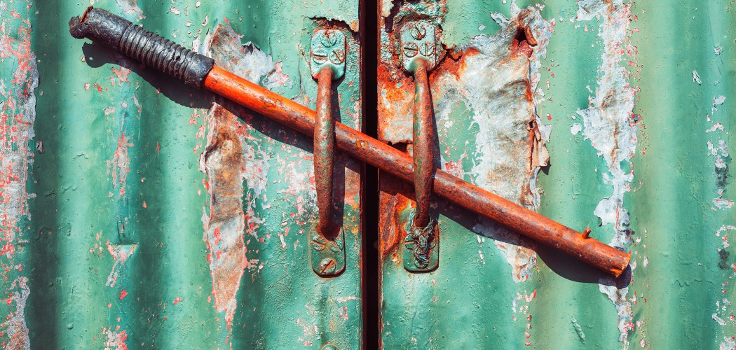 Handles on a rusty green door, bolted shut with an old handle - abstract